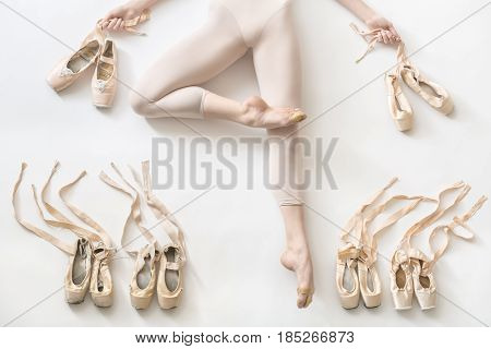 Pretty ballerina lies in passe on the white floor in the studio. She wears a light dance wear and holds ribbons of the shoes in her hands. On the sides of her legs there are ballet shoes. Horizontal.