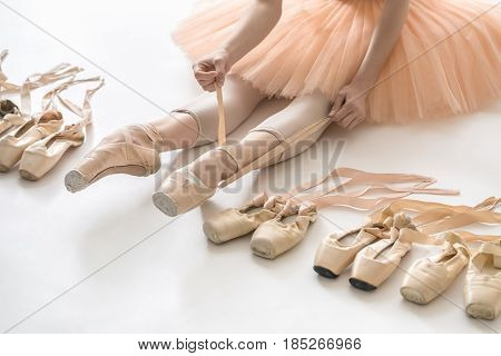 Woman who is ballerina sits on the white floor and dresses a beige pointe shoe in the studio. She wears a light dance wear and a peach tutu. On the sides there are ballet shoes. Closeup. Horizontal.