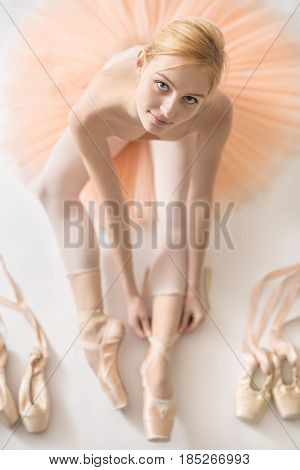 Smiling ballerina sits on the white floor and dresses a beige pointe shoe in the studio. She wears a light dance wear and a peach tutu. On the sides there are ballet shoes. Top view photo. Closeup.