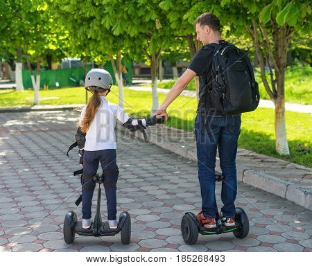 Young father and daughter riding electric mini hoverboard in park. Family concept