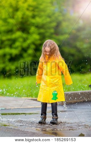 Little girl in raincoat and boots playing in the rain.