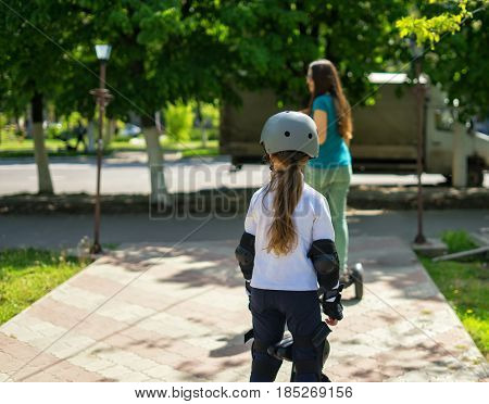 Young mother teaching her daughter riding electric mini hoverboard in park. Family concept. Riding together.