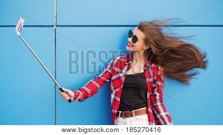 Fashion pretty cool girl makes self portrait on smartphone over blue background. Outdoor