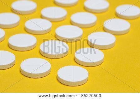 The hite pills on yellow paper background