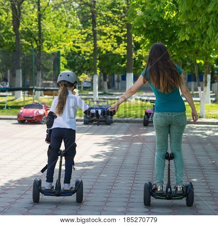 Young mother and daughter riding electric mini hoverboard in park. Family concept. They are holding hands.