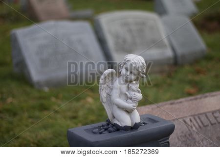 Exterior daytime up close shallow depth of field winter stock photo of angel headstone in Mount Hope cemetery in Rochester, New York in Monroe County