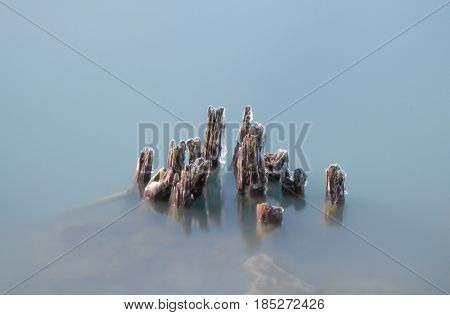 Daytime long exposure stock photo of remnants of icy wooden pylons protruding from Lake Erie in Buffalo, New York in Erie County.