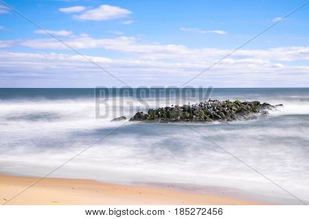 Long exposure daytime stock photo of rocks off the shoreline of beach in Spring Lake, New Jersey on sunny winter morning.