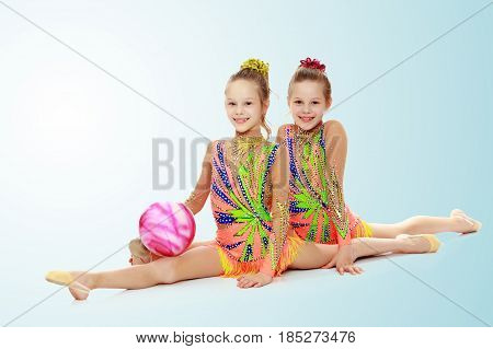 Two adorable little twin girls, gymnastics in the sports school. Girls beautiful gymnastic leotards. They do the splits.On the pale blue background.