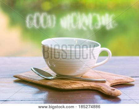 Hot coffee with smoke of good morning wording on wooden saucer and on wooden table with reflection of mountain and tree in water under morning sunlight
