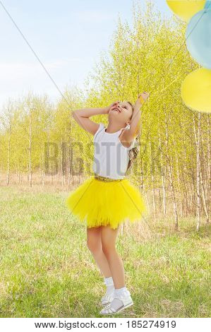 Pretty little blonde girl in a short bright yellow skirt and white blouse.Girl holds in hands balloons , She looks at them from the bottom up.Against the background of the summer landscape.