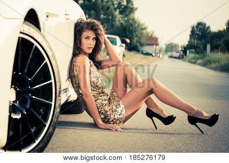 summer fashion girl in golden dress sit by car on road in high heels
