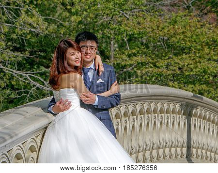New York April 29 2017: Young Asian couple is posing for a picture during a wedding album photoshoot in Central Park.
