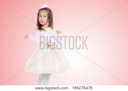 Dressy little girl long blonde hair, beautiful pink dress and a rose in her hair.She spreads her hands aside.Pale pink gradient background.