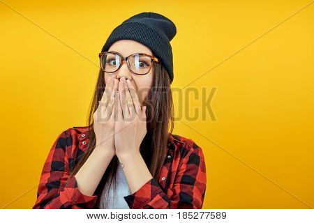 Hipster girl cover mouth with her hands. Young surprised woman over yellow background.