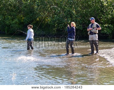 Alaska, USA - August 11, 2008; Alaskan salmon fishing. Two young women and a man guide salmon fishing in small river in Alaska.