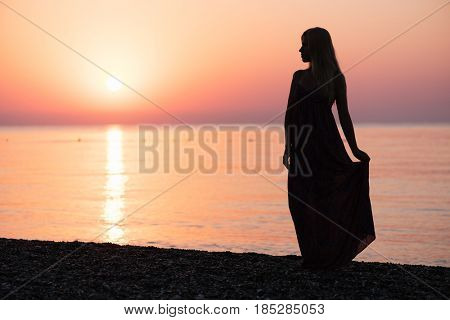 Silhouette of a blonde girl in a sundress. Beautiful dawn by the sea