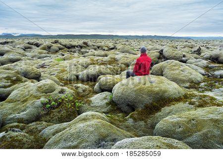 Traveler in a red jacket sits on a moss. Lava field on the south coast of Iceland, Europe. Tourist attraction. Amazing in nature. Cloudy summer day