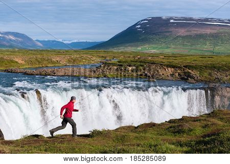 Godafoss waterfall. Beautiful landscape in Iceland. Guy in a red jacket runs happily by the river