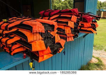 A life vest or life jacket is hung for drying out.A sleeveless jacket or vest that is filled with buoyant material and used as a life preserver.