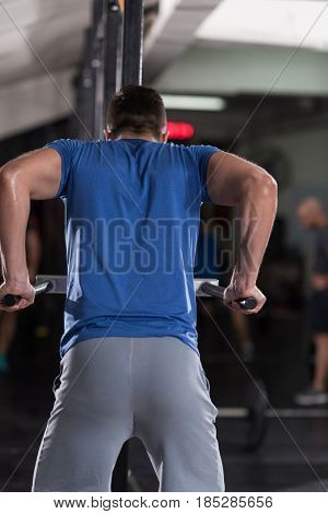young muscular bodybuilder working out in gym doing exercises parallel bars  Concept sport
