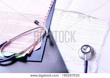 Medical stethoscope on electrocardiogram on desk