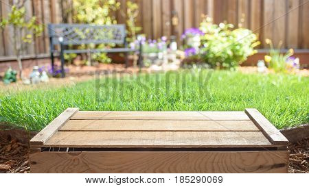 Empty wooden crate with blurred backyard on background. Display of products.