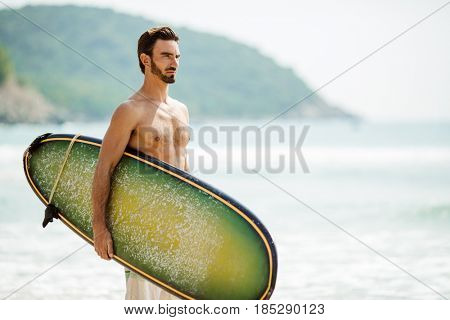 Surfer man with surfboard on sea coast.