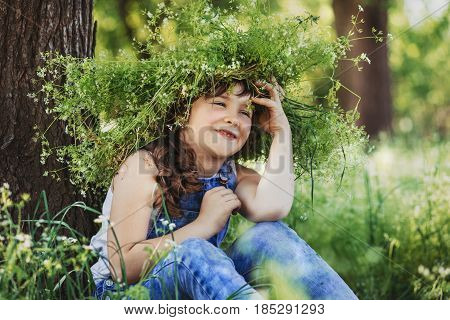 Little happy girl with a wreath on a head sitting by a tree in the woods. Wreath of wild flowers on the head of a child