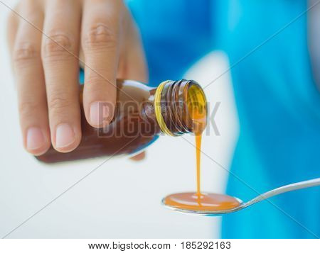 healthcare people and medicine concept - woman pouring medication or antipyretic syrup from bottle to spoon