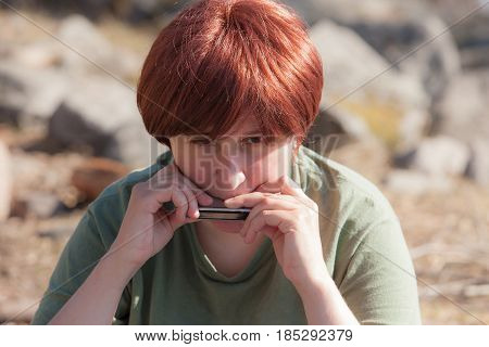Portrait of a woman playing a harmonica