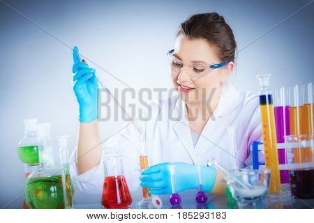 Laboratory technician measures chemical liquid with a pipette. Lab equipment and glass. Scientific research concept.