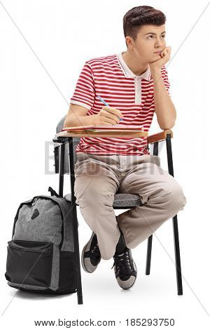 Bored teenage student sitting in a school chair isolated on white background