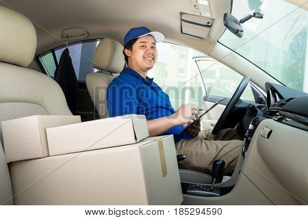 Delivery Man With Cardboard Box Checking Document List In Van And Parcels On Seat Outside The Wareho