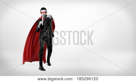 A businessman in a superhero red cape and a mask throwing punches in the air on white background in high contrast shot. Business motivation. Fight for success. Effort and results.