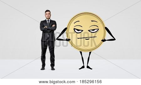 A serious businessman standing with arms crossed beside a large humanoid gold coin. Financial troubles. Importance of money. Profitable venture.