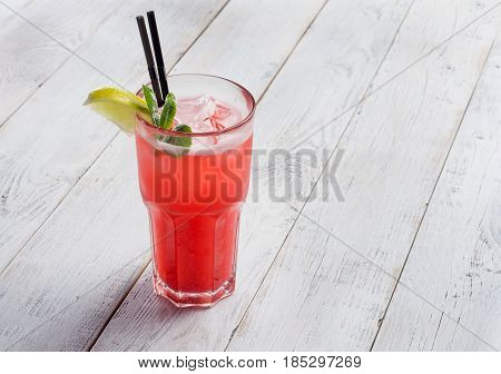 red limonade in glass on white wooden background. With space for your text .