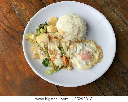 Stir-fried Mixed Vegetables With Tofu And Fried Egg With Rice In White Dish On Wooden Background.  V