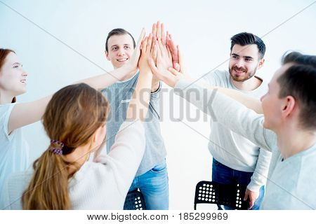 Success and winning concept - group of people giving high five