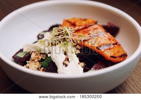 Appetizer of baked beetroot and grilled pear in porcelain plate, toned image