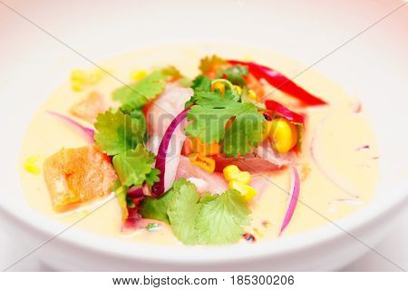 Sea bass ceviche with pumpkin, cilantro, corn and onion in deep plate, Peruvian food, toned image