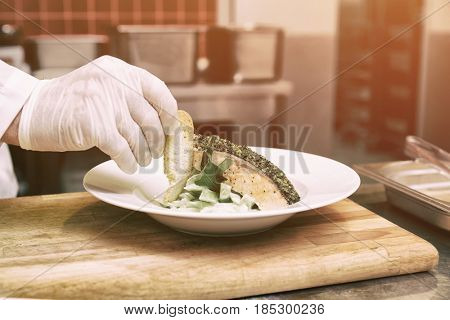 Chef is decorating a fish dish with grilled bread slice, toned image