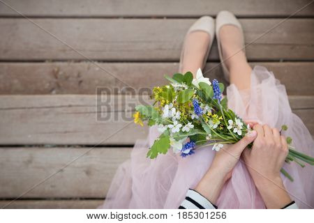 Top view on woman holding beautiful bunch of spring flowers. Girl with bouquet of daffodils apple tree flowers and other garden flowers. Summer and spring concept. Selective focus.