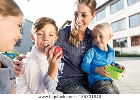 Mother and kids at school having breaktime with apple and lunchbox