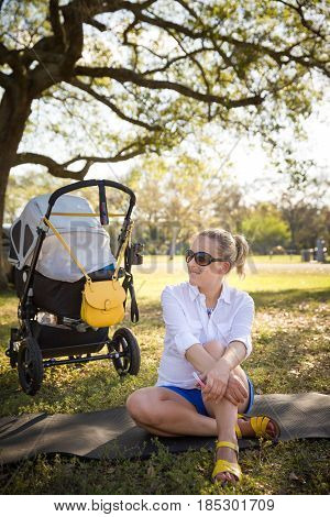 Young beautiful mother sitting on the grass in the park with her baby sleeping in the stroller. Woman with a stroller walking outdoors and enjoying sunny summer day.