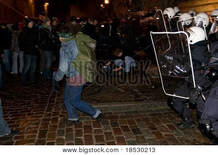 RIGA, LATVIA, JANUARY 13, 2009: After peaceful protest to call for early elections many anti-government demonstrators tried to break into parliament. Aggressive crowd and police had fight in downtown.
