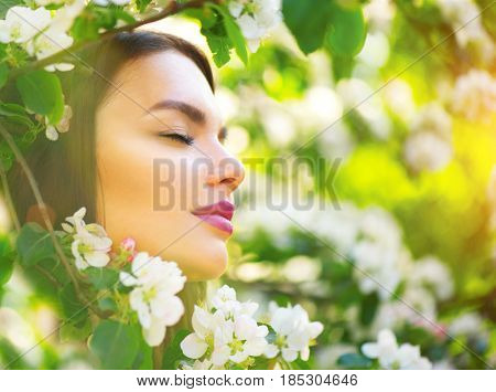 Beautiful Young Woman enjoying nature in blooming apple tree and smiling. Orchard with flowers. Outdoors. Healthy Smiling Girl in spring garden. Allergy free concept