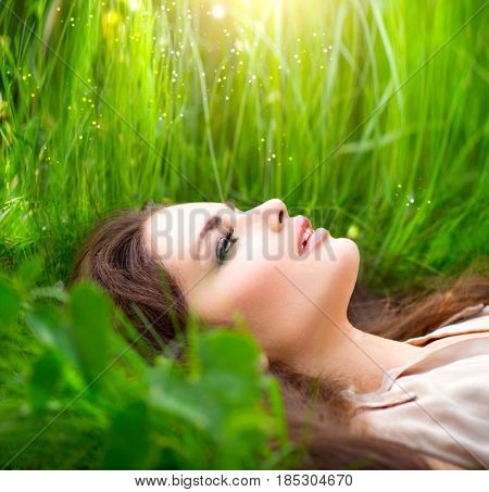 Beauty woman lying on the field and dreaming. Beautiful Girl lying on the meadow. Enjoying nature. Spring or Summer Green Grass