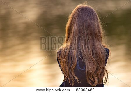 Teen brunette girl with long hair standing Against the water background. Symbolizing resentment disappointment and despair