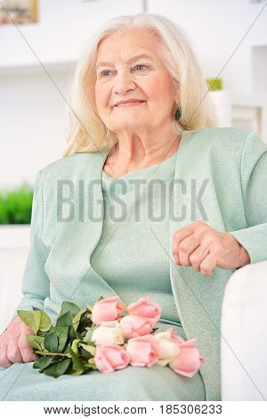 Beautiful senior woman at home with a bouquet of roses. Happy Mother's Day. Beauty, fashion. Happy retirement.